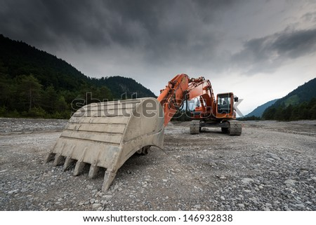 perspective of digger power shovel in red on gravel - stock photo