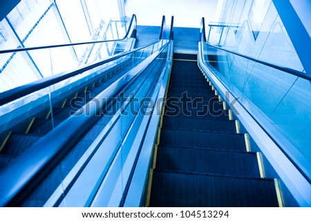 Perspective of escalator toned in blue color. - stock photo