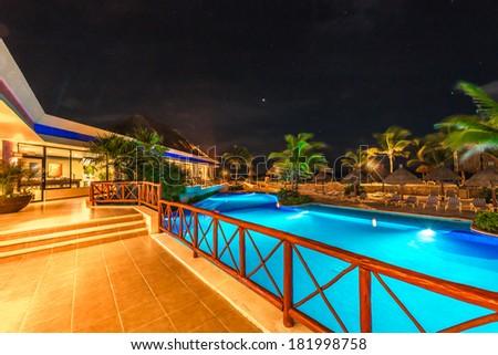 Perspective of promenade between swimming pool and a restaurant at luxury caribbean resort at night, dawn time. Bahia Principe, Riviera Maya, Mexico. - stock photo