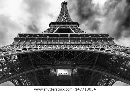perspective of the Eiffel tower from the bottom with a cloudy and bleak sky
