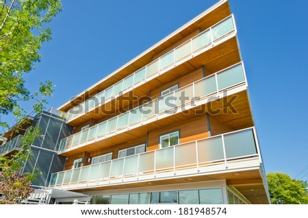 Perspective, outlook of the modern glass, wood and steel building, house with the balconies on perimeter.  Exterior design. - stock photo
