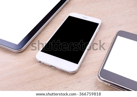 Perspective smartphone and tablet blank screen on wooden background - stock photo