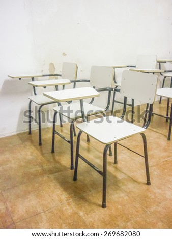 Perspective view of a bunch of empty classroom white chairs. - stock photo