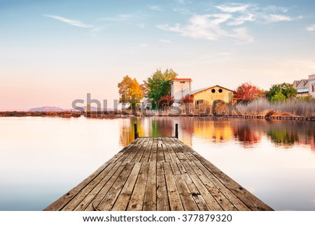 Perspective view of a wooden pier on a small pond near a countryside with reflections at sunset - stock photo