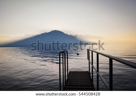 Perspective view of a wooden pier on the pond at sunset, Switzerland