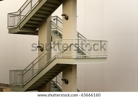 Perspective view of a zig-zag pattern of an exterior steel stairway against an empty wall
