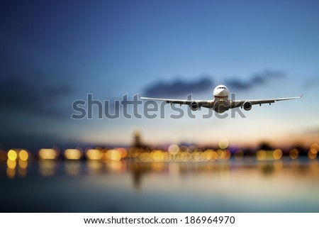 perspective view of jet airliner in flight with bokeh background - stock photo