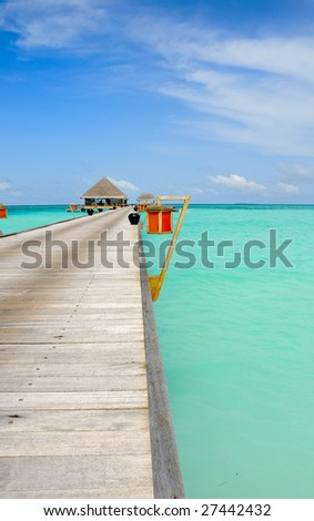 perspective view of jetty leading over turquoise ocean - stock photo