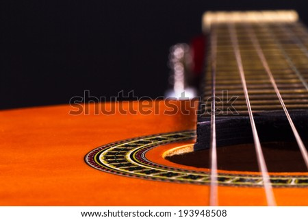 Perspective view of orange wooden classical acoustic guitar over black background. - stock photo