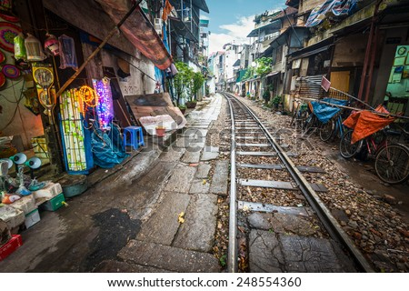 Perspective view of railway running along narrow street with houses in Hanoi, Vietnam. Unusual solution of transport problem. Dangerous neighborhood for people. Travelling and tourism. - stock photo