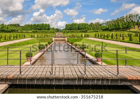 Perspective view of the wooden bridge and green flower beds in the park under a blue sky with white clouds near Frederiksborg castle, Hillerod, Denmark - stock photo