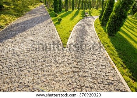 Perspective view of two cobblestone roads thinking deciding hoping for best taking chance - one of the road has an ancient park bench - stock photo