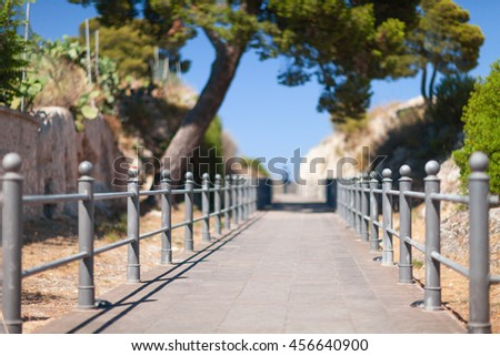 Perspective view of walking track towards the sea. Blurred silhouette on the horizon. Cagliari, Italy. - stock photo