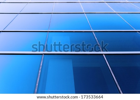 Perspective view to blue background of glass building skyscraper - stock photo
