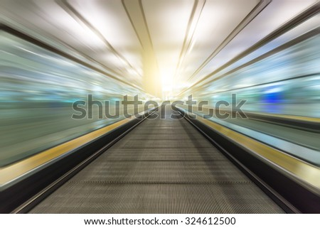 Perspective wide angle black and white view of modern light blue illuminated and spacious high-speed moving escalator with fast blurred trail of handrail in vanishing traffic motion - stock photo