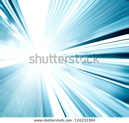 Perspective wide angle view of modern light blue illuminated and spacious  high-speed moving escalator with fast blurred trail of handrail in vanishing traffic motion - stock photo
