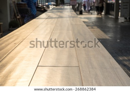Perspective wood table top in front of shop at evening. - stock photo