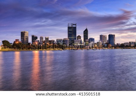 Perth city CBD across wide Swan river at sunrise. Illuminated towers of capital city of Western Australia reflecting lights in still waters.