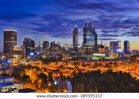 Perth city CBD at sunrise as seen from hights of Kings park. Skyscrapers of capital of Western Australia illuminated above city highways