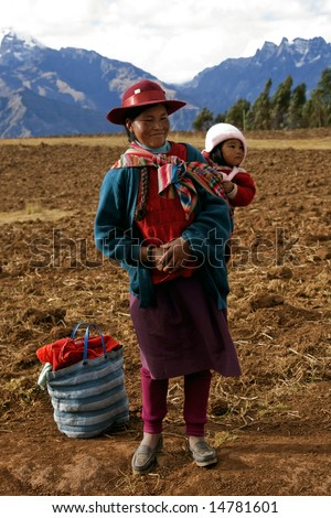 PERU - AUGUST 1: A native Peruvian woman demonstrates how to wrap and carry a child August 1, 2007 in Sacred Valley, Peru.