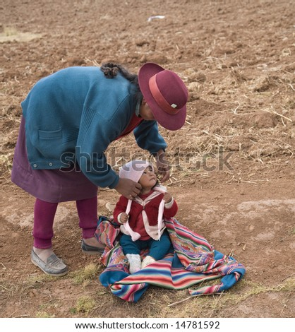 PERU - AUGUST 1: A native Peruvian woman prepares to demonstrate how to wrap and carry a child August 1, 2007 in Sacred Valley, Peru.