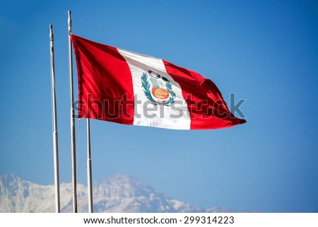 Peruvian flag waving in the air in Arequipa, Peru with El Misti volcano visible in the background