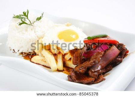 "Peruvian  food beef, whit potatoes, egg, and rice. ""Lomo Saltado"" - stock photo"