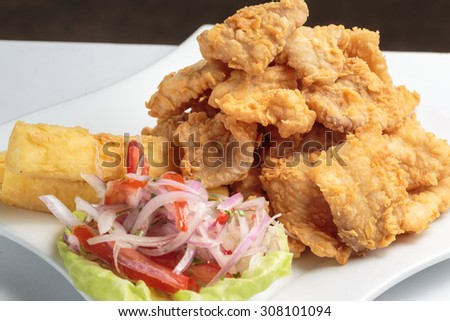 "Peruvian food,, ""chicharron de pescado"": Fried fish served with batata and onion salad. - stock photo"
