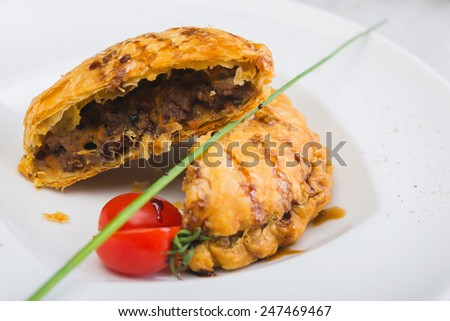 Peruvian snack called Empanada pie filled with ground beef meat and vegetables on a wooden table