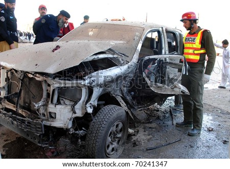 PESHAWAR, PAKISTAN - JAN 31: Police officials inspect wreckage of vehicle which was destroyed in suicide bomb explosion after explosion at Kohat road  on January 31, 2011in Peshawar.