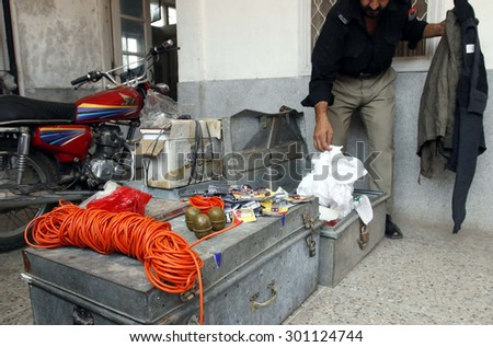 PESHAWAR, PAKISTAN - JUL 29:  Police officials show arrested of criminal, weapons and explosive materials to media persons during press conference on July 29, 2015 in Peshawar.