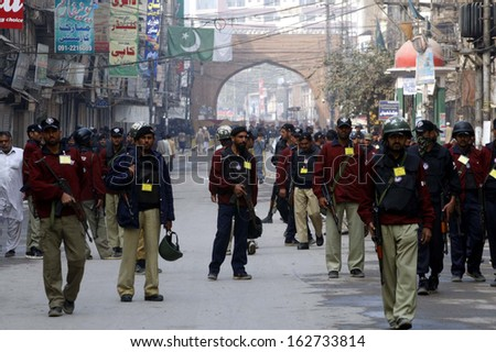 PESHAWAR, PAKISTAN - NOV 13: Police officials escort to guard religious processions in connection of 8th Moharram-ul-Haram, pass through a road on November 13, 2013 in Peshawar.