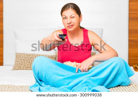 pessimistic emotional girl watching TV on the bed - stock photo