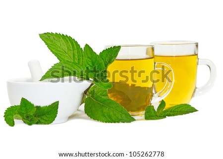 Pestle and mortar with freshly crushed lemon balm leaves used to brew healthy refreshing mint or lemon balm tea or tisane with medicinal and aromatherapy properties - stock photo