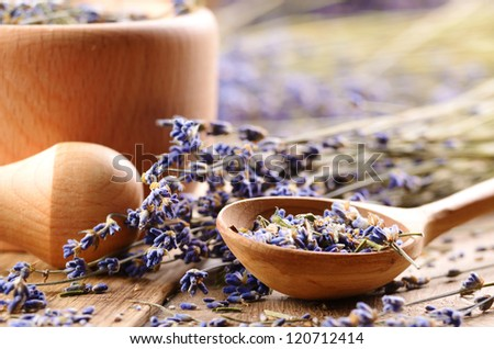 Pestle and mortar with lavender flowers on the oak table - stock photo