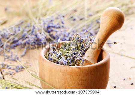 Pestle and mortar with lavender on the oak table - stock photo