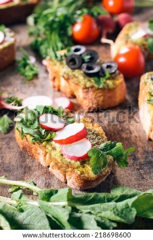 Pesto and radish bruschettas on the woden background,selective focus  - stock photo