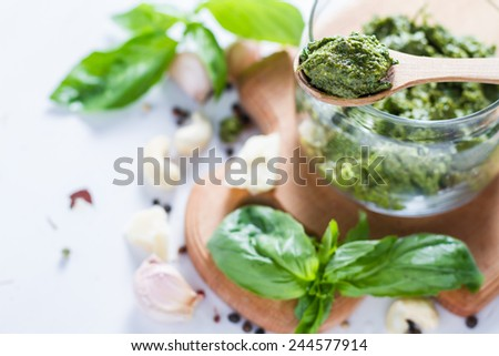 Pesto in glass jar on wood board, garlic, basil, pepper, cheese on white wood background, top view - stock photo