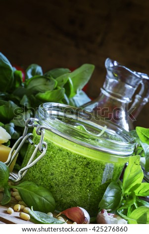 Pesto sauce in a glass jar, cheese, basil, garlic, nuts on a dark background, selective focus