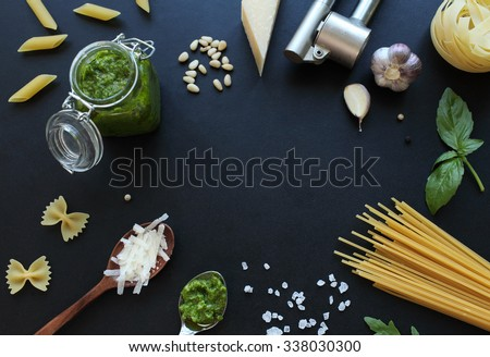 Pesto sauce ingredients and raw pasta on black board. Food frame with free space in the middle. - stock photo