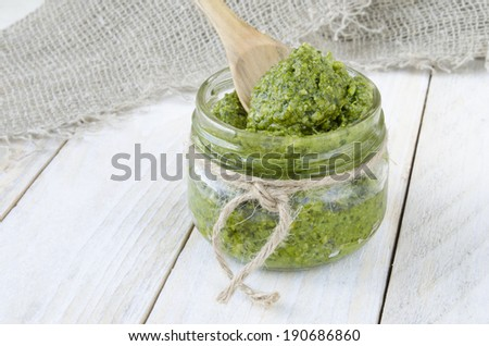 Pesto sauce with wood spoon on white wood boards  - stock photo