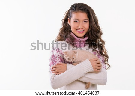 Pet and smiling girl. Chinese appearance of a teenager. Ginger cat in hugs. Happy pet. Cute animal for girls. White background. Studio photo shoot. Cool wallpaper.