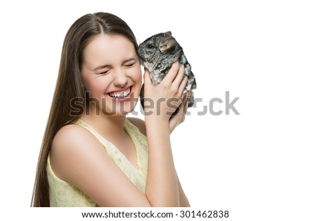 Pet chinchilla kissing beautiful cheerful teenage girl. Isolated over white background. Copy space. - stock photo