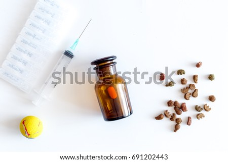 Pet cure concept. Pills, ampoule, syringe and animal feed on white background top view