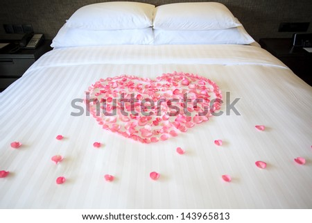 Petals of roses on a white honeymoon bed