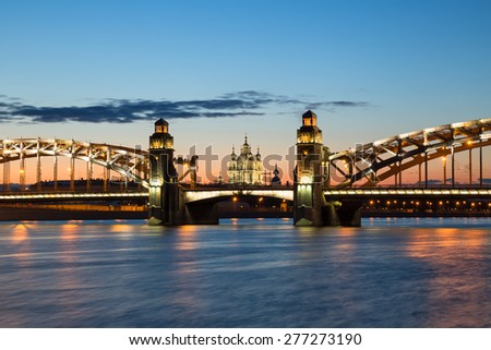 Peter the Great Bridge and Smolny Cathedral in Saint-Petersburg with lights in the summer night - stock photo