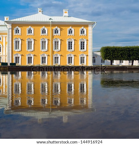 Peterhof Grand Palace with beautiful reflection on the water's edge. Peterhof, Russia - stock photo