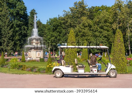 PETERHOF, RUSSIA - AUGUST 19, 2015: Electric taxi driver is waiting for tourists near Roman fountain in The Eastern Part of The Lower Park in the State Museum Preserve.