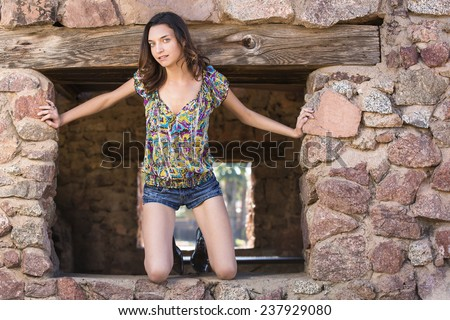 Petite brunette girl posing and looking out in an old brick window - stock photo