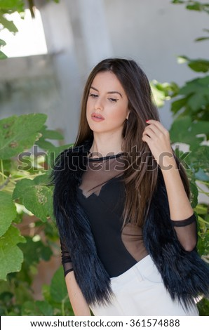Petite young woman with very long hair wear bodysuits and lamb fur vest - stock photo